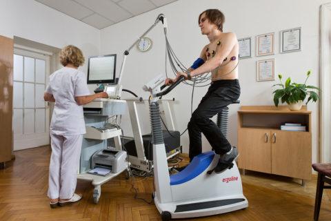 На фото мужчина проходит тестовые исследования сердечной деятельности на велоэргометре